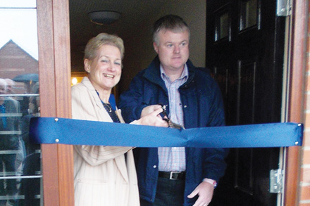 Cllr Wallace cuts the ribbon at St Vincent's House